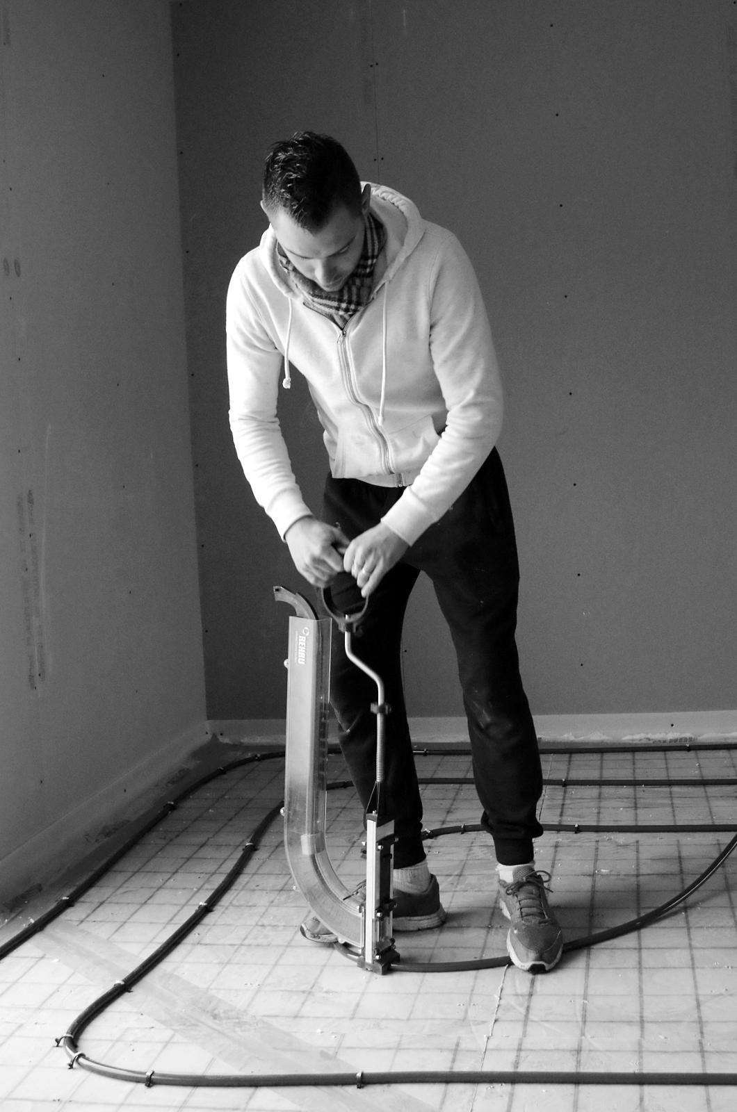 un plombier installe le plancher chauffant